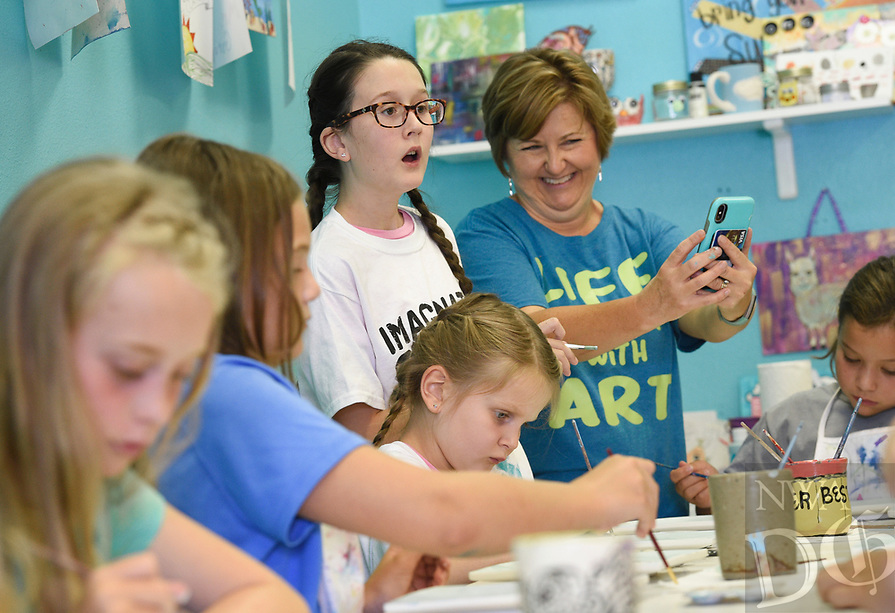 NWA Democrat-Gazette/CHARLIE KAIJO Imagine Studios owner Melanie Hewins (center right) takes pictures as Ella Koster 10 of Bentonville (center left) reacts during an art camp, Monday, August 5, 2019 at Imagine Studios in Rogers.<br /> <br /> Imagine Studios owner Melanie Hewins held an art camp called Unicorn Dreams. Kids decorated unicorn themed plates and unicorn and rainbow magnets. The camp runs till Thursday. Kids learn how to use acrylic paints and water colors and canvas and ceramic painting.
