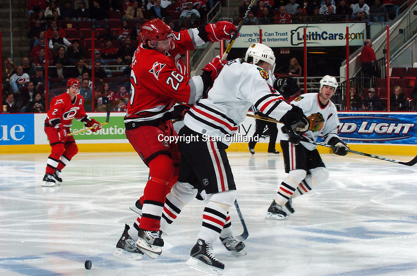 Carolina Hurricanes' Erik Cole (26) hits the Chicago Blackhawks' Jaroslav Spacek (6) of the Czech Republic at mid-ice during their game Tuesday, Dec. 13, 2005 in Raleigh, NC. Carolina won 5-3.