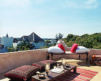 Cushions and a rustic bench are arranged on the roof terrace creating an informal space for open-air relaxation