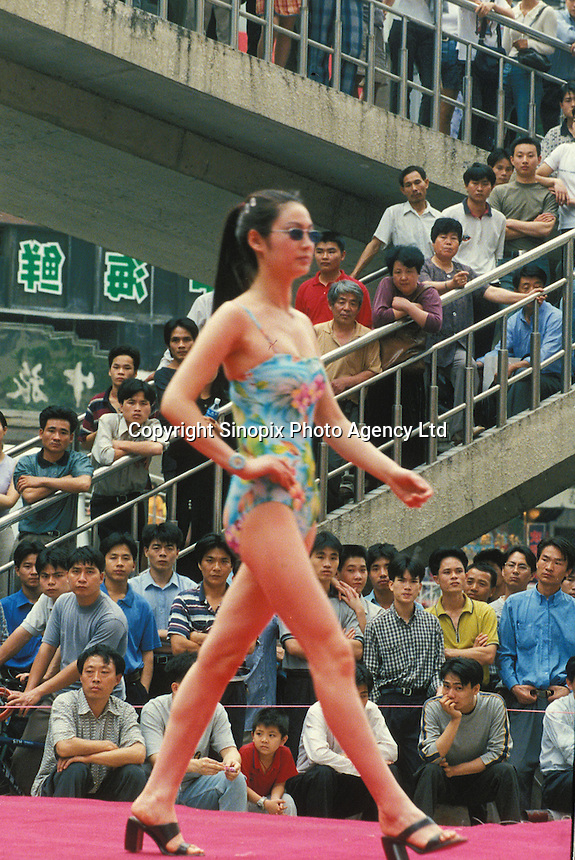 Men crowd around a women's swim wear fashion show in Shenzhen. An average gender inbalance 118 males to 100 females caused by the strict Child Policy and the preference for boys means that there is a shortage of women in China.