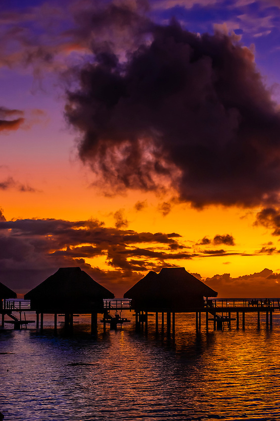 Overwater bungalows at sunset, Hilton Moorea Lagoon Resort, island of Moorea, French Polynesia.