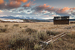 An old cabin and fence decay in a prairie as seen during a colorful sunset near the Anaconda area of Montana.