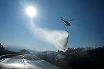 An helicopter drops water at the site of a wildfire in Fumaces, near Ourense on August 25, 2013. (c) Pedro ARMESTRE