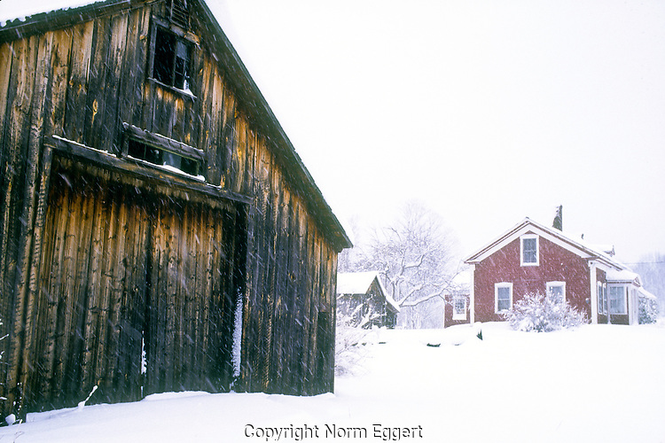 Old Barn and a Red House in Winter Storm