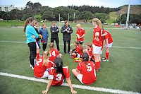 The Sacred Heart team listen to the halftime team talk during the Wellington girls college football bronze playoff final between Sacred Heart College (red) and Wellington High School (green and gold) at Wakefield Artificial Turf,  Wellington, New Zealand on Wednesday, 21 August 2013. Photo: Dave Lintott / lintottphoto.co.nz