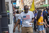 A shopper wearing Old Navy passes workers and supporters marching through the streets of Soho on Saturday, June 29, 2013 stopping off at various clothing retailers, including the Gap's Old Navy, protesting the companies' refusal to the Bangladesh Safety Accord guaranteeing better safety conditions in Bangladeshi factories. In April a collapse of an enormous garment factory killed over 1000 workers. (© Richard B. Levine)