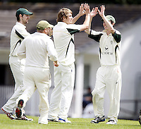 Freddie Issit (L) of North London is high fived by a team mate after dismissing Mitchell fry during the Middlesex County Cricket League Division Three game between Wembley and North London at Vale Farm, Wembley on Sat May 31, 2014