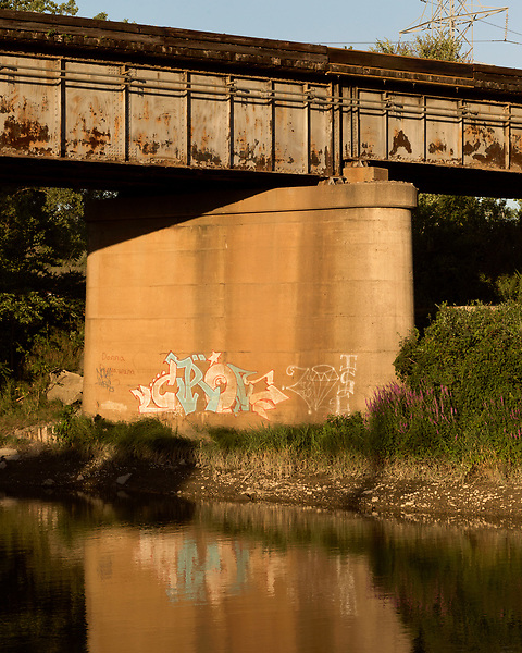 August 5, 2016. Flint, Michigan.<br />  Late afternoon along the Flint River. <br />  In April 2014, the city of Flint switched its water source from the Detroit Water and Sewerage Department to using the Flint River in an effort to save money. When the switch occurred, the city failed to have corrosion control treatment in place for the new water. This brought about a leaching of lead from pipes into the water, increasing the lead content in the drinking water to levels far above legal limits. After independent sources brought this to light, the city admitted the water was unsafe and legal battles have ensued between resident and the local and state governments.