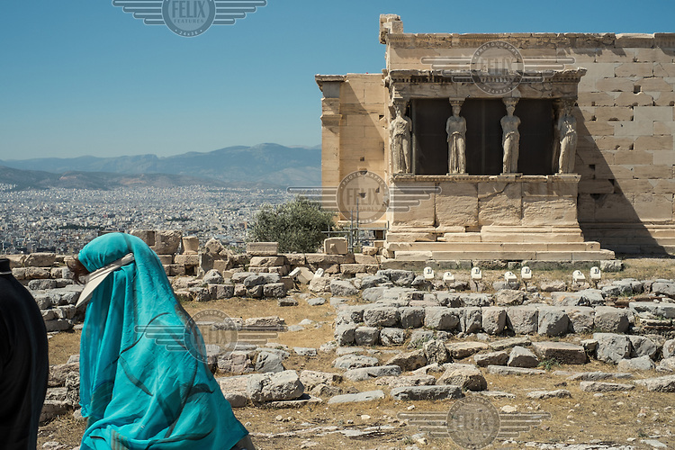 ATHENS, GREECE:  a tourist walks by the Caryatids at the Achropolis archaeological site.