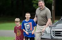 Michael McCollum<br /> 8/2/18<br /> David Overman arrives with his sons Ryan,13,(middle) and Alex,7, at the reveal ceremony where it was announced to Ryan Overman of west Knoxville that The Wish Connection is granting Ryan&rsquo;s wish to go to Washington DC and visit the White House at Carl Cowan Park, 10058 S Northshore Dr, Knoxville, TN&nbsp;, Thursday, August 2, 2018 at 5:45pm. Approximately 50-60 people attended, including the Overman family, friends, and AT&amp;T Employees. The Bearden High School Cadets also attended and lead the pledge of allegiance.<br /> &nbsp;The AT&amp;T Wish Connection is going to send Ryan, his family, and his service dog to Washington DC and while they are gone, the group of volunteers will be doing a makeover on his bedroom and turn it into the &quot;Oval Office&quot; at the White House.<br /> Ryan was born two weeks prematurely on May 13, 2005.&nbsp; During the pregnancy he was classified as high risk due to a measured lack of growth and, after a brief stay in the hospital, he came home weighing only 4 lbs 5 oz.&nbsp; His development was much slower compared to his peers, such as not learning to walk until he was well over a year old, and he was much smaller. The Overman family worked with Tennessee Early Intervention Services (TEIS) when Ryan was about one year old and with their help they were able to get Ryan enrolled through TEIS to receive Occupational, Physical, and Speech Therapy.&nbsp; When Ryan turned three he transitioned from TEIS to the Knox County Early Intervention Program and began attending a special school to continue his therapies until he was old enough to enroll at Cedar Bluff Elementary and now is at Cedar Bluff Middle School. In 2016, Ryan was diagnosed to have retinitis pigmentosa, a degenerative disease of the retinas that under the best of circumstances causes severe tunnel vision, but more commonly results in complete blindness.<br /> &nbsp;Despite the physical difficulties that Ryan has had to endure over the last thirteen years, he continually brightens the lives of those around