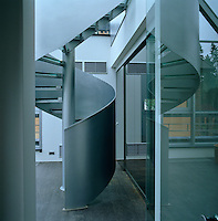 A polished metal spiral staircase winds from the hall to the first floor