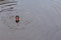 Boy in black water of River in Suriname