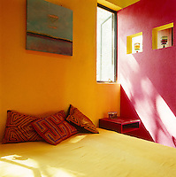 Light pours through the small window in this colourful yet simple bedroom