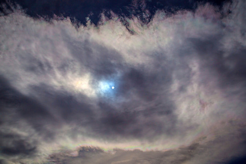 The midday moon is illuminated by the sun through the clouds in Southern Utah, Earth