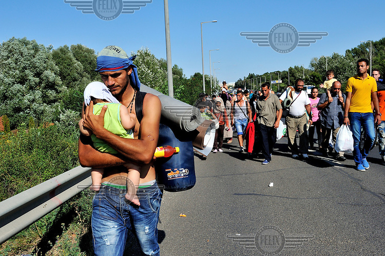 A Syrian refugee supports his baby's head as he carries him along the highway, with other refugees, several kilometres after leaving Budapest. Thousands of refugees, mostly from Syria, had been stranded for days in Budapest at the city's main Keleti train station. The government had closed the borders with Western Europe to them, and cancelled all trains that might take them to Germany and beyond. On Friday, 4 September 2015, in a gesture of defiance and frustration, hundreds of refugees set out to walk to Vienna, a distance of about 250 kilometres. In reaction, in the night, the Hungarian government changed policy and brought refugees to the border with Austria, not only those on the road, but also those at Keleti station and others being held in various camps. /Felix Features