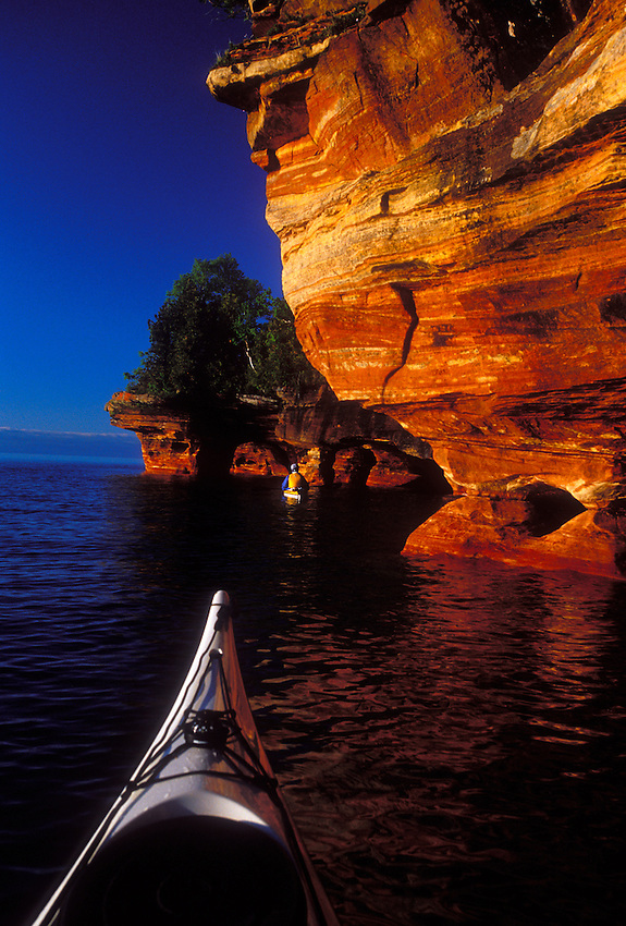 Sea kayakers explore the sandstone cliffs and caves on Devils Island in Apostle Islands National Lakeshore near Bayfield, Wis.