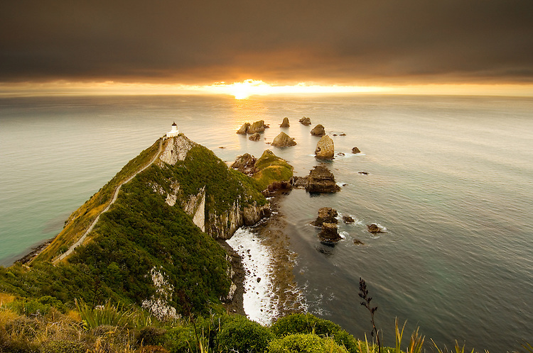 Nugget Point lighthouse at dawn looking out to sea, The Catlins, Otago, South Island, New Zealand - stock photo, canvas, fine art print