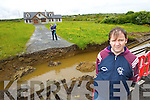 William Dennehy outside his house with his wife Eileen and son Liam after their footpath was washed away in a flash flood in Duagh on Tuesday evening.