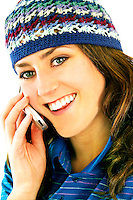 Young woman wearing a cap laughing and talking on cell phone