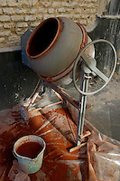 Bucket full of prepared red ochre pigment, Seville, Andalusia, Spain.