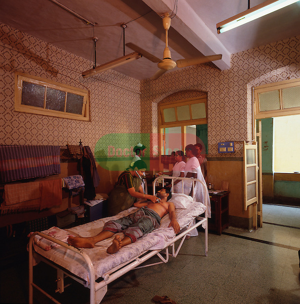 Doctor examining patient after his operation in an Indian public hospital. Madras/Chennai..