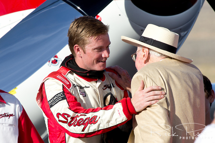 Strega Pilot and 2 time Gold Unlimited Champion air race pilot Steve Hinton greets legendary pilot Bob Hoover in the winners circle after the championship race.