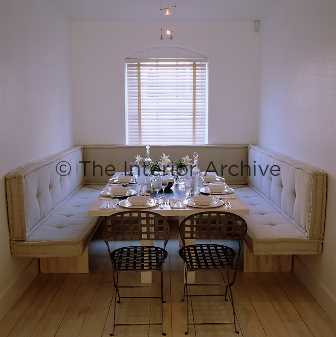 A U-shaped banquette surrounds a laid table in this simple and intimate dining alcove