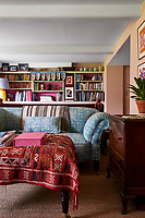 The sitting room is a glorious mismatch of colour, pattern and texture with built-in shelving providing plenty of bookshelf space.