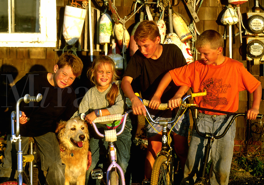 Group of kids on bikes with pet dog.