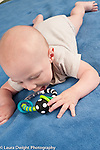 5 month old baby boy reaching to touch toy, on stomach