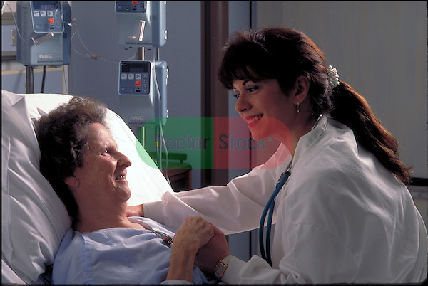 smiling nurse comforting patient in hospital bed