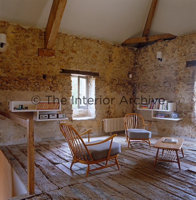 The vintage Ercol table and chairs both contrast and compliment the exposed floors and walls of this rustic living room in a converted granary