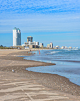 South Padre island beach in the winter. You can see children building sand castle and playing in the surf along with people fishing. The skyline is full of hotels, and condos.