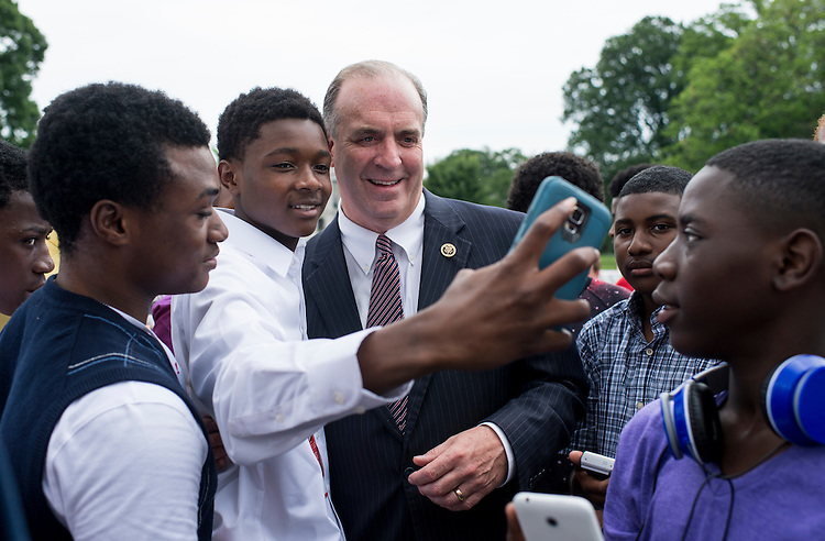 UNITED STATES - JUNE 17: Rep. Dan Kildee, D-Mich., poses for selfies after speaking to a group of students from the Saginaw Public Schools Centric Program on the House steps on Wednesday, June 17, 2015. (Photo By Bill Clark/CQ Roll Call)