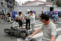 A man pleads his case to a traffic police officer after someone hit his scooter and ran in Shanghai, China..28 Jun 2006