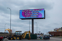 """A billboard reading """"Stay safe during Covid-19 / Stay home if sick / wash your hands / social distance"""" visible from Interstate 93 is seen in the parking lot of the IBEW Local 103 parking lot in Dorchester, Massachusetts, on Mon., March 23, 2020. The ongoing Coronavirus (COVID-19) global pandemic has caused cities and towns to put up public health messages such as this billboard in public areas."""