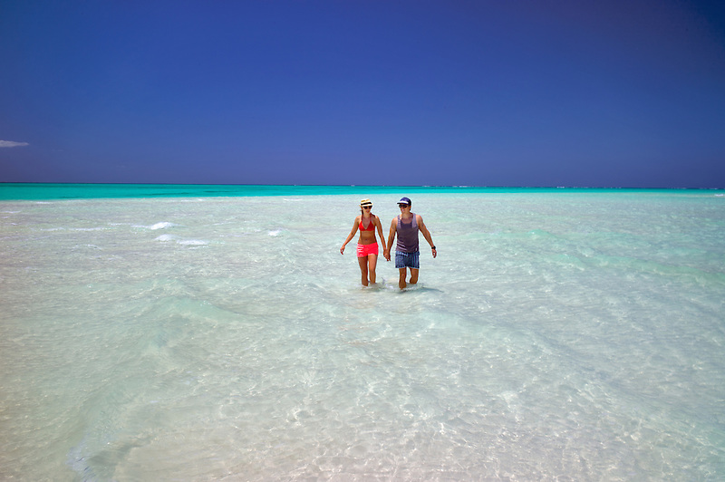 Couple in water of beach of Fort George Cay, an uninhabited island. Turks and Caicos.
