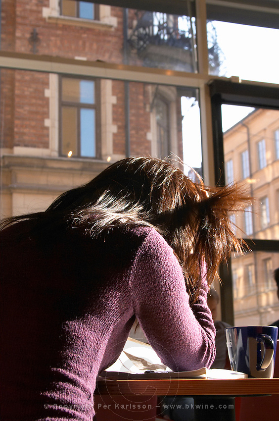 A young woman sitting in a cafe with a cup of coffee reading a newspaper in a purple sweater pulling her hair. Typical end of 18 century buildings in the background. Stockholm, Sweden, Sverige, Europe