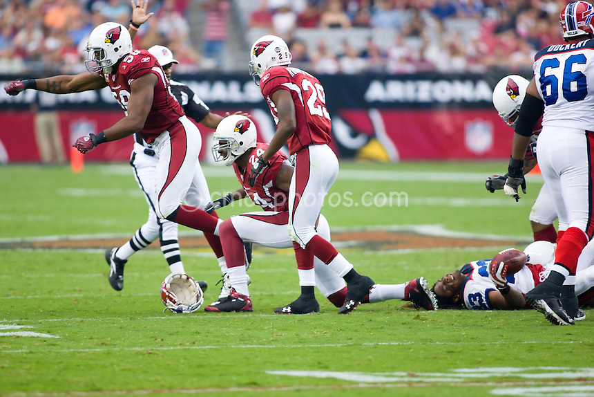Oct 5, 2008; Glendale, AZ, USA; Arizona Cardinals linebacker Karlos Dansby (58), safety Adrian Wilson (24), and defensive back Dominique Rodgers-Cromartie (29) celebrate a helmet-removing hit on Buffalo Bills running back Marshawn Lynch (23) in the third quarter of a game at University of Phoenix Stadium.  The Cardinals defeated the Bills 41-17.