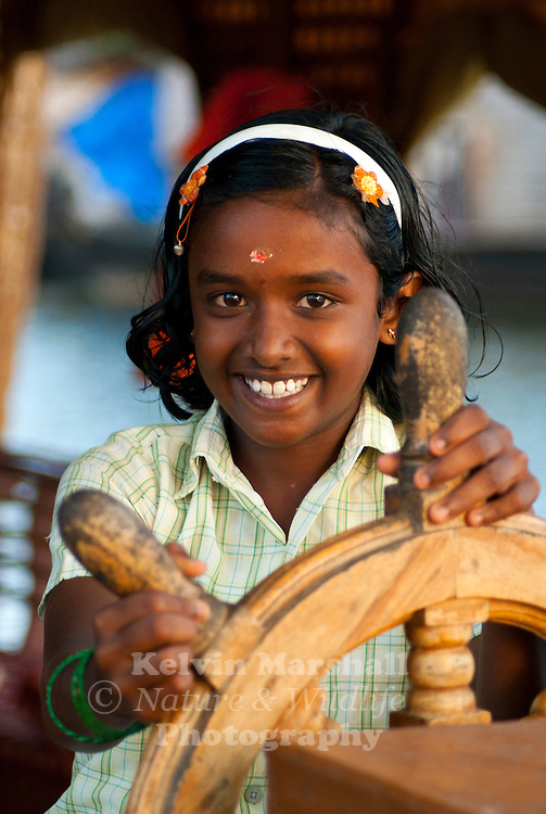 Young attractive Indian girl helps her father to steer his house boat throughout the Kerala backwaters.