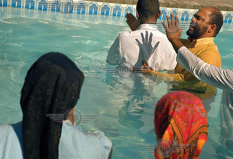 A man is submerged at a religious ceremony as women look on in Redelinghuys.