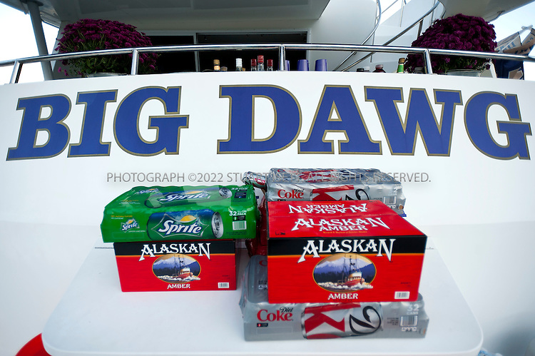 """9/24/2011--Seattle, WA, USA...Beer and drinks are loaded up on the yacht 'Big Dawg"""" before the boat sets sail across Lake Washington from Mercer Island to Husky Stadium...The 'Big Dawg', owned by Lisa and Tim Kittilsby, is the biggest, most prominent boat that attends regular boat tailgate parties on docks near the UW (University of Washington) Husky Stadium. Up to 500 boats will tie up outside Husky Stadium on football game days, ranging from from small boats to huge yachts. The Big Dawg is a 92-foot, two-story yacht that dominates the tailgate parties...The tradition started when Lisa and Tim Kittilsby's parents, Frank and Jeanie Miles, took a 23-foot boat called The Mixer to a game over 40 years ago...©2011 Stuart Isett. All rights reserved."""