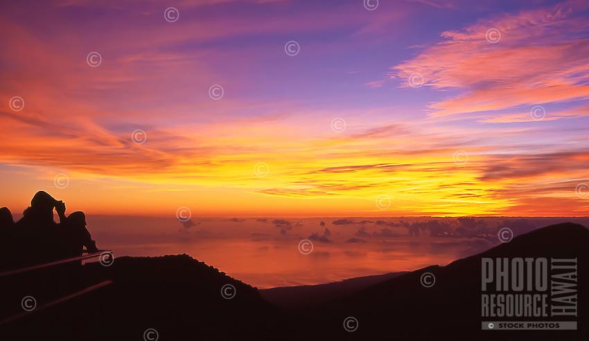 People enjoy the sunrise at Kalahaku Overlook in Haleakala National Park, Maui.