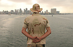 "With the San Diego skyline receding into the distance, a marine stands at attention - part of a ceremony known as ""manning the rails"" - as the amphibious assault ship USS Belleau-Wood aboard which he stands slips out of San Diego harbor on its way towards Iraq.  The marine is one of the 2,220 members of the 11th Marine Expedition Unit which will arrive in Iraq in mid-July for a scheduled seven-month-deployment to replace elements of the 1st Armored Division which has been in Iraq for nearly a year-and-a-half."