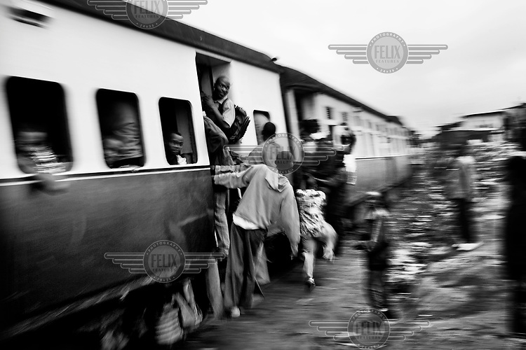 The overcrowded passenger train runs once in the morning and once in the evening, carrying Kiberans to and from work in downtown Nairobi. Over 25 percent of Nairobi's population live in Kibera, an area that covers less than one percent of the city. Although the population of the slum is over one million, it is recognised officially as a 'squat', or illegally occupied land, which allows the government to ignore the basic needs of the inhabitants.