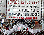 MICHAEL SMITH/WTE..Rookie saddle bronc rider Lydell Norris takes a break before competition behind a sign in the comboy ready area Saturday.