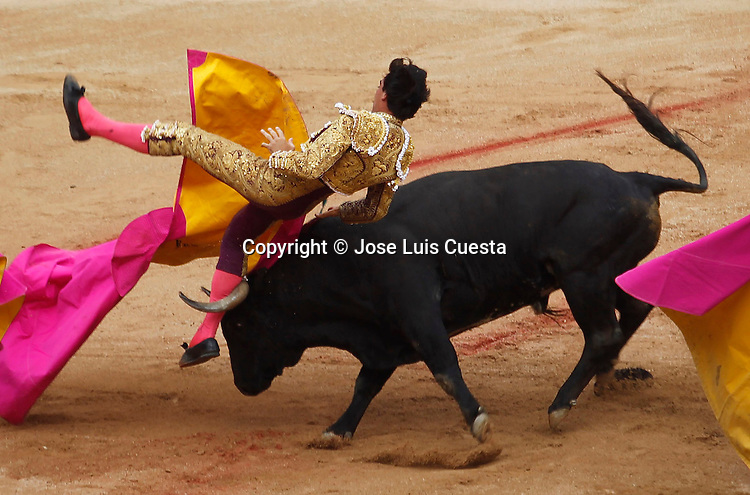 The bullfighter is hooked by the bull during San Fermin´s bullfight, Pamplona, Spain. San Fermin festival is worldwide known because the daily running bulls and bullfights.