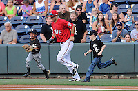 Youth ballplayers run out onto the field as Cole Sturgeon (35) of the Greenville Drive is announced to the crowd before a game against the Augusta GreenJackets on Friday, July 11, 2014, at Fluor Field at the West End in Greenville, South Carolina. (Tom Priddy/Four Seam Images)