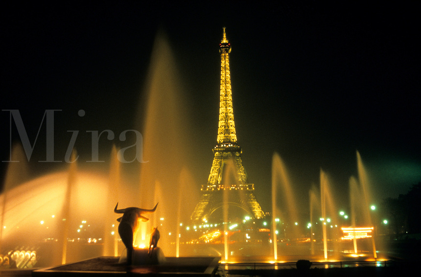 the famous Eiffel Tower through fountains in Paris France at night