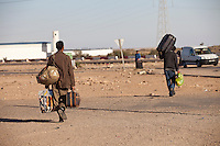 Tunisie pres du Djiba Camp UNHCR de refugies libyens a la frontiere entre Tunisie et Libye , libyens en attent d'etre envoyes dans leur camp....Tunisia close to Djiba UNHCR refugees camp  Tunisian and Libyan border  libyan refugees waiting for their final camp destination....Tunisia nei pressi del campo profughi di Djiba al confine tra tunisia e Libia  Profughi libici appena giunti e  in attesa di essere inviati in uno dei campi profughi si allontanano con bagagli